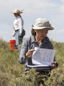 woman with clipboard reviewing information in field