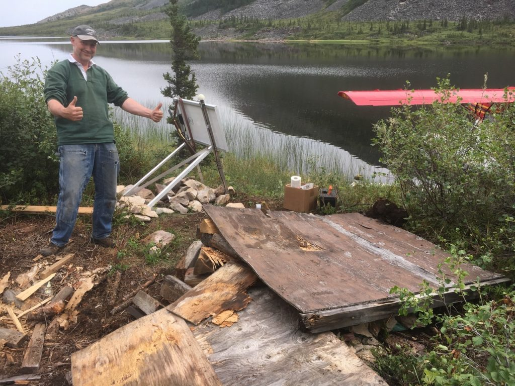 Man giving a thumbs up near a pile of wood