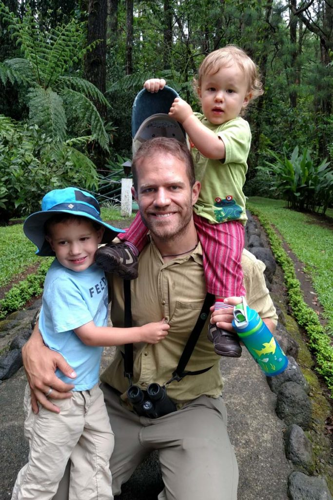 man and children in rainforest