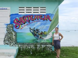lady standing next to sign for charter fishing company in Belize.