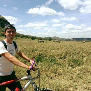 Young man on bike with zebra standing in field behind him.