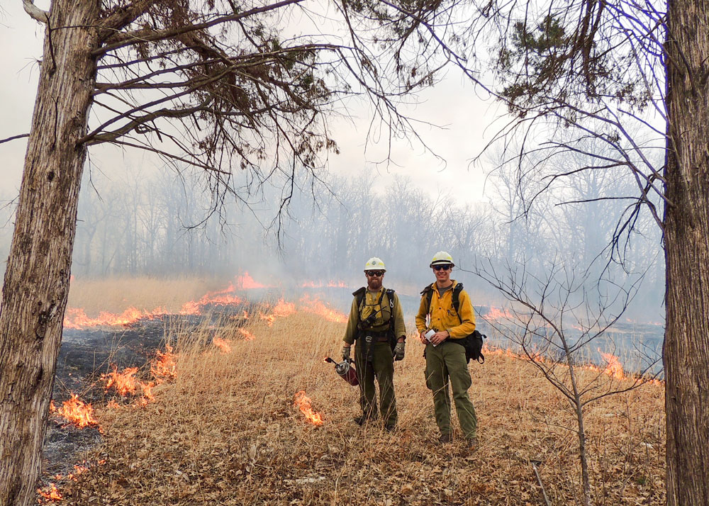 Student firefighters stand within a burn area