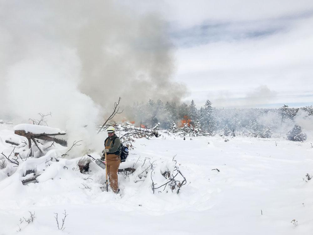 man lights wood in a snowy meadow
