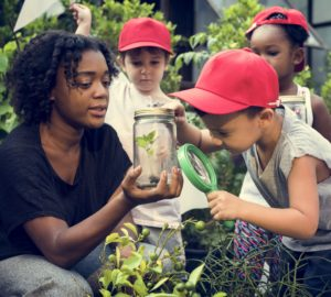 a woman explains conservation research to a group of children. she is holding a jar with a plant and a child is using a magnifying glass to look at it