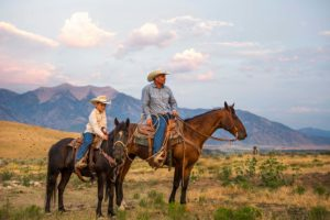 image of father and son on horses at dude ranch, representing an element of agritourism