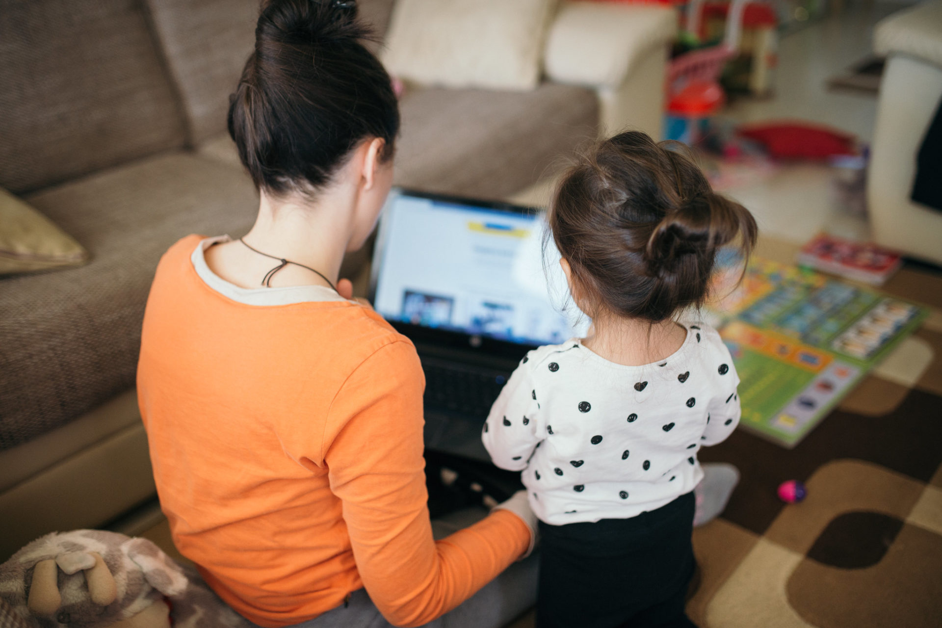 mom teaches daughter for work on laptop