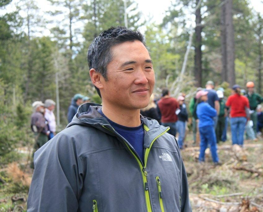 CSU Professor Tony Cheng in a forest, with people in the background