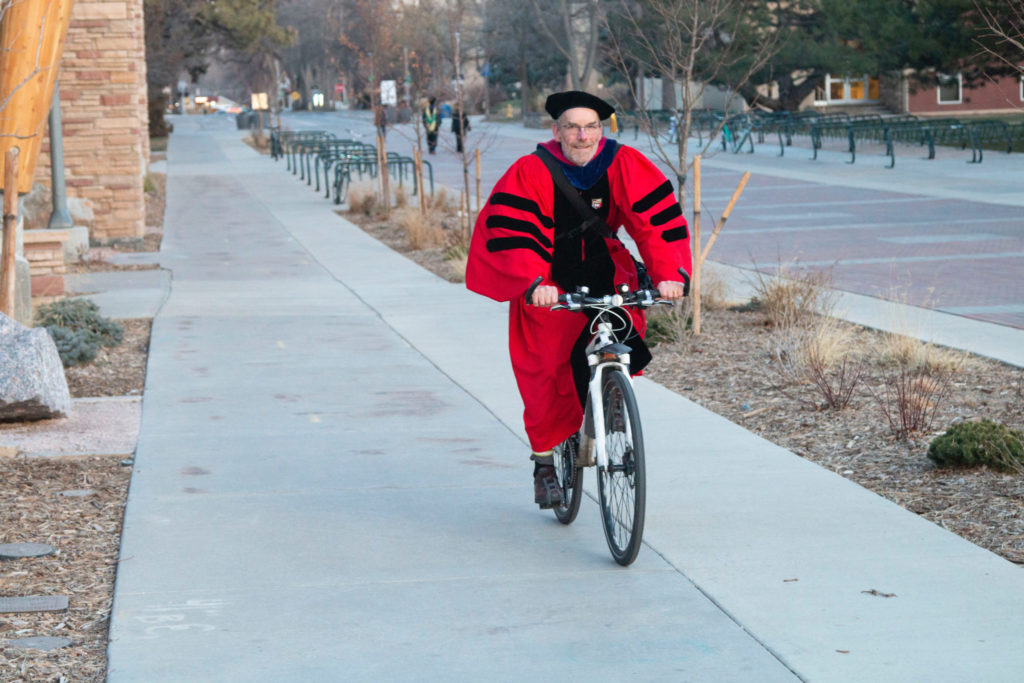 Dean John Hayes riding a bike with his commencment regalia on